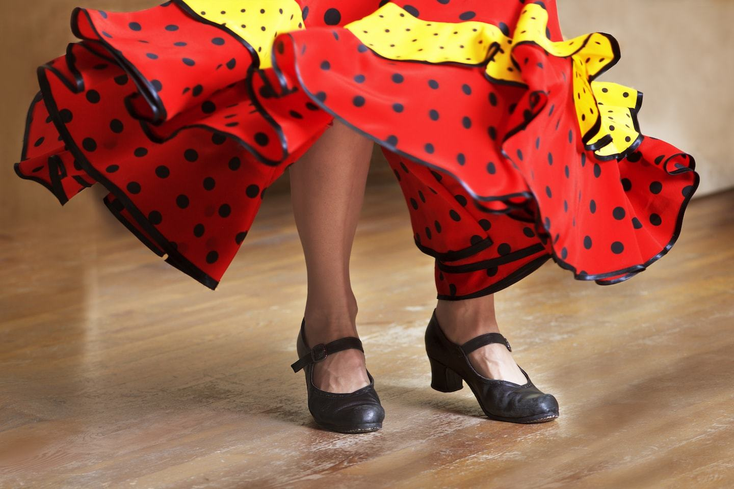 view of a woman's feet and bottom of her red and yellow dress as she dances flamenco