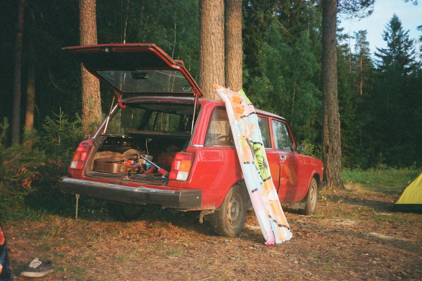 car with open trunk and camping equipment