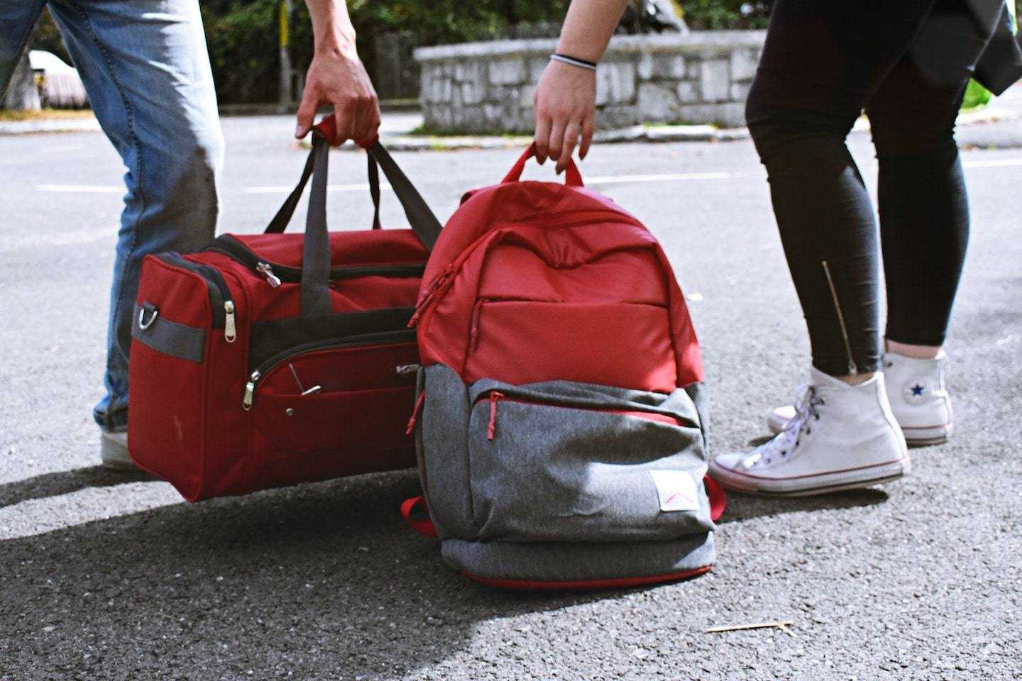 two people, one with duffel bag the other with backpack