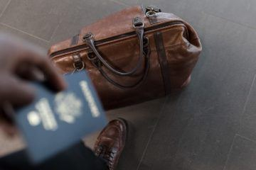 person with leather duffel bag and passport