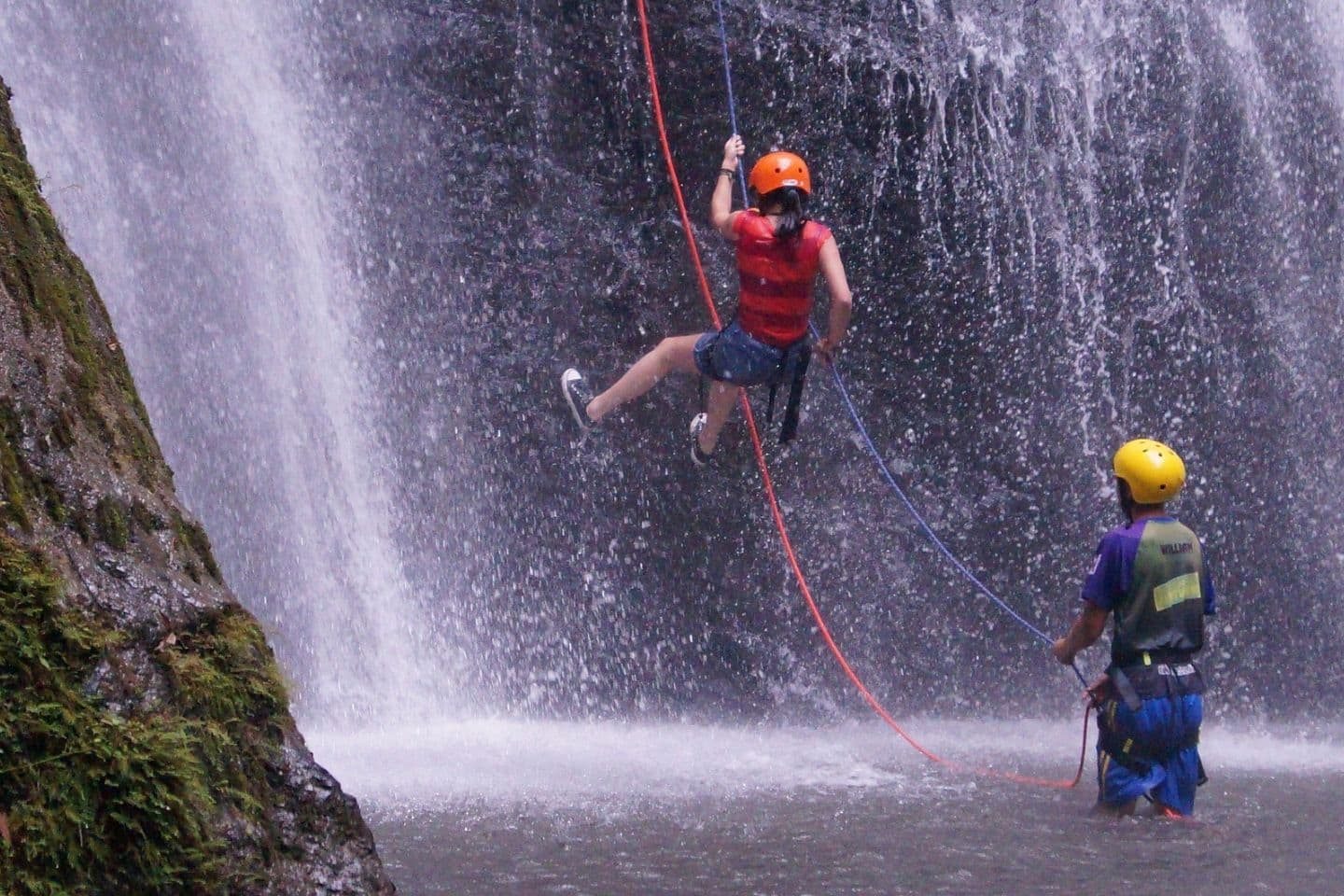woman canyoning down a waterfall