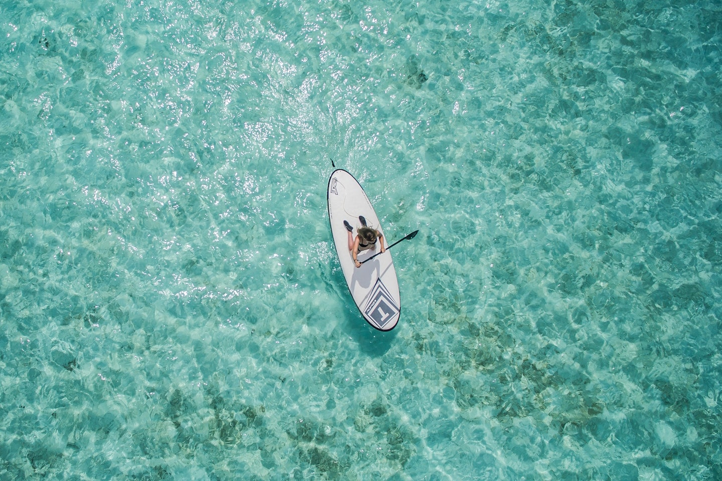 person paddle boarding taken by a drone