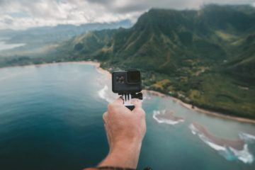 person holding a gopro in front of mountains and water
