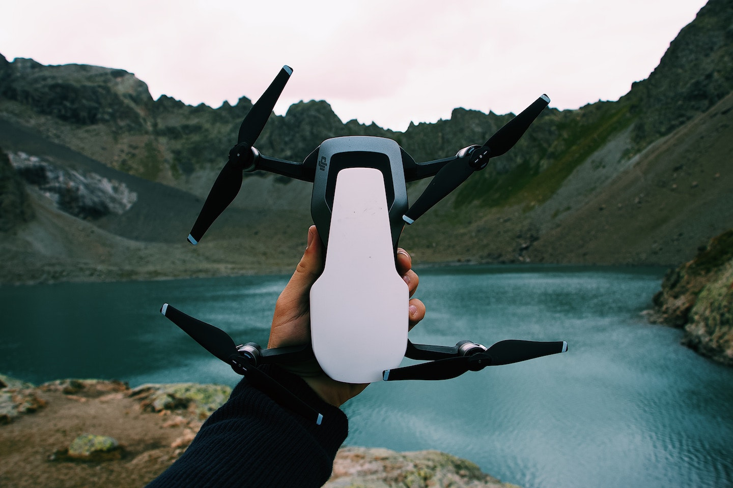 person holding drone in front of water and mountains