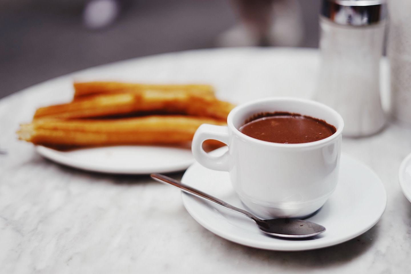 cup of chocolate with churros in the background