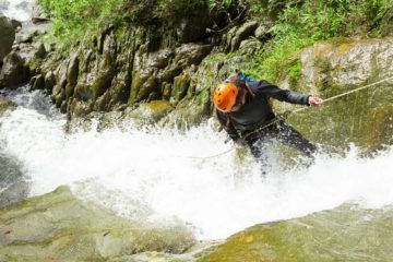 man canyoning down waterfalls