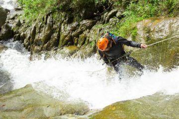 man canyoning down waterfalls