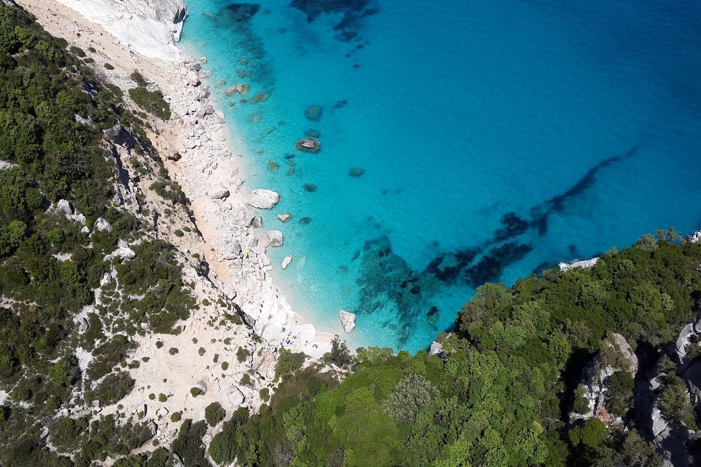 turquoise water with beach and surrounding greenery