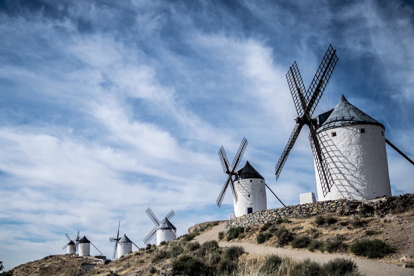 large white windmills against a blue sky in consuegra spain