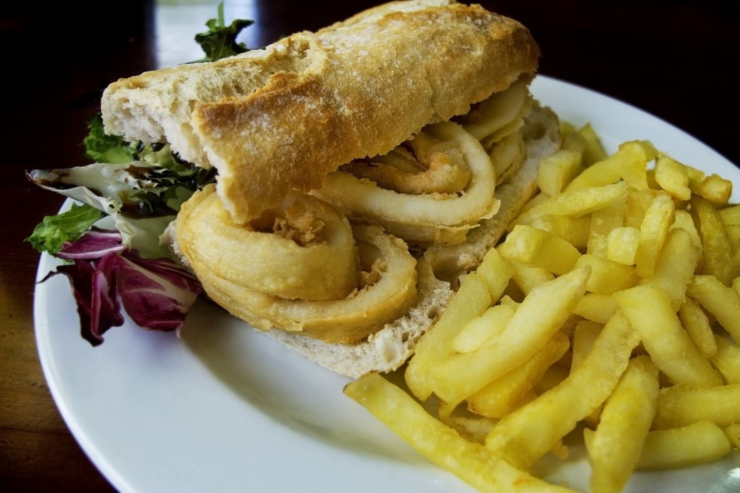 baguette sandwich with fried squid and a side of french fries