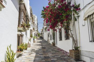 cobblestone streets with white buildings and flowers in marbella spain