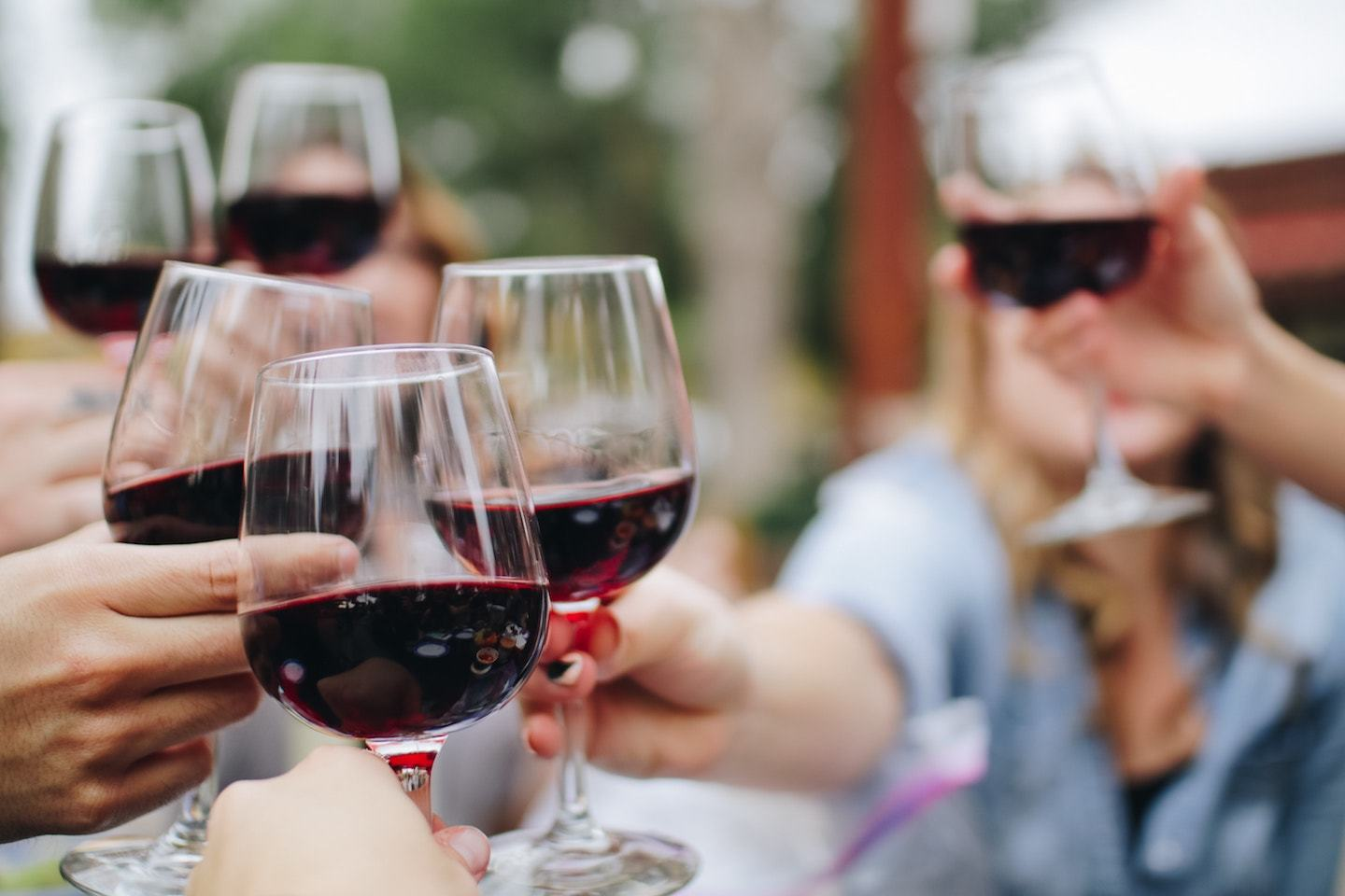 many people cheersing with glasses of red wine