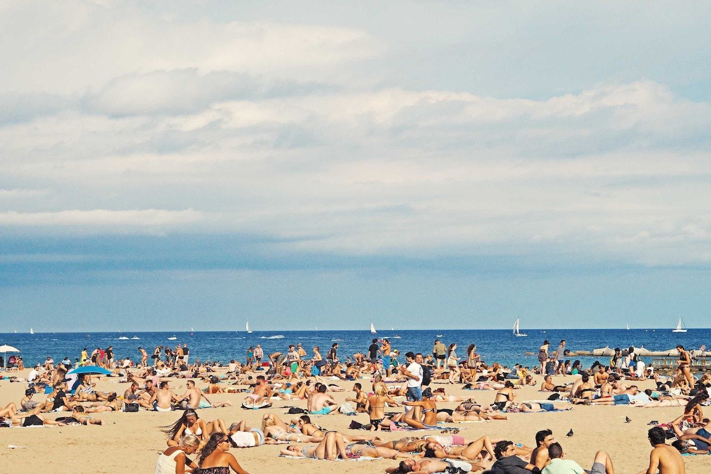 lots of people laying in the beach under blue sky