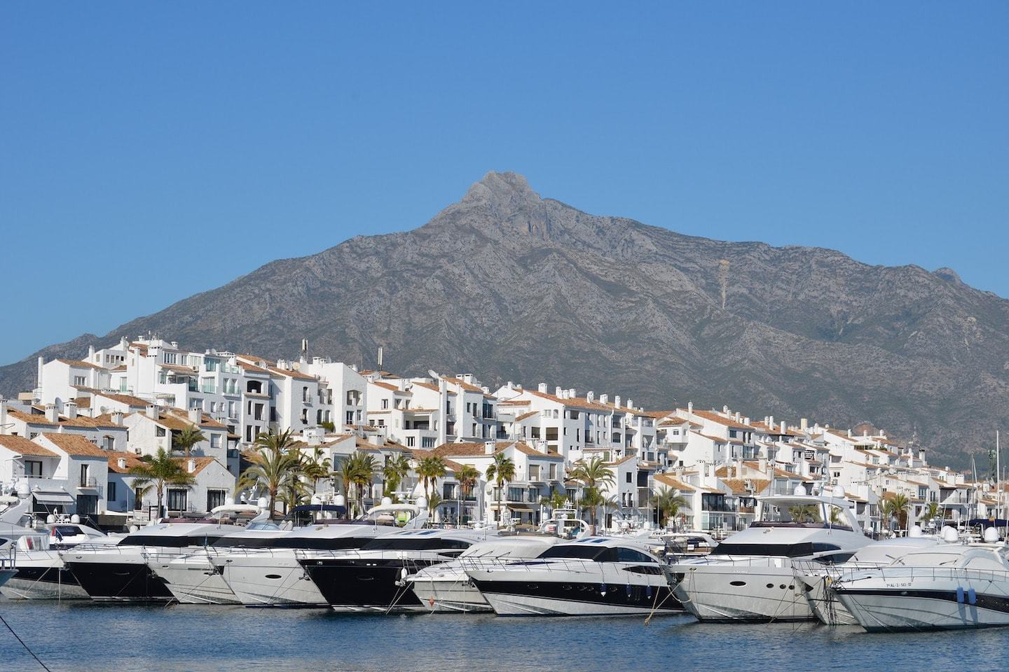 port with docked ships with mountains and houses in background