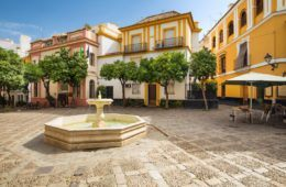 colorful buildings surrounding small town square with fountain