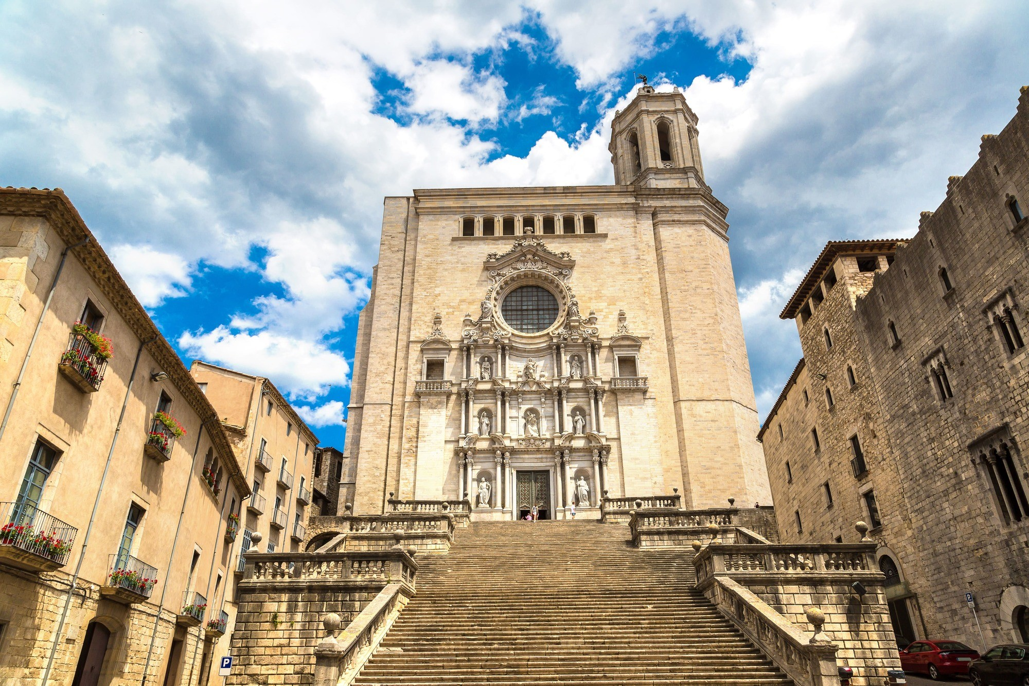 steps leading up to large stone cathedral with blue sky and clouds behind