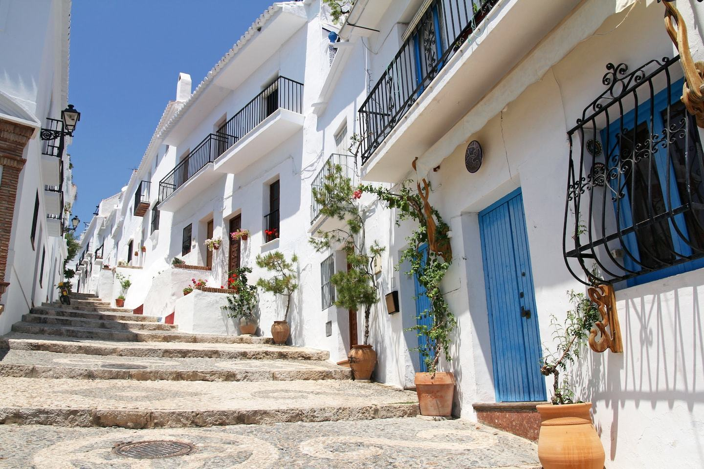 white washed buildings with blue doors and plants in spain