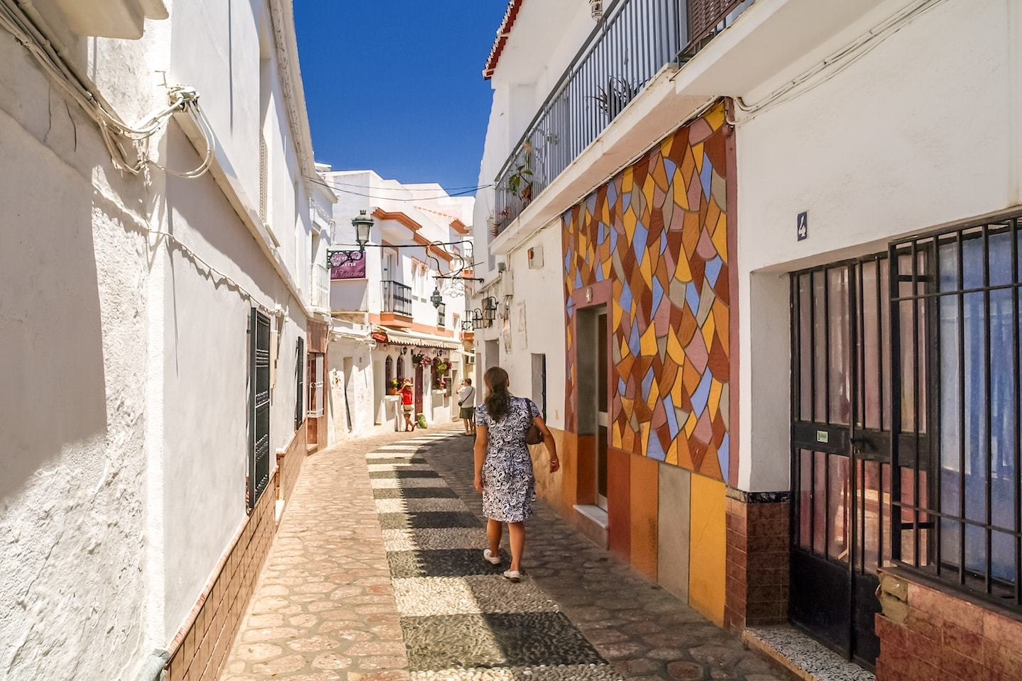 woman walking between white walls and patterns in nerja spain