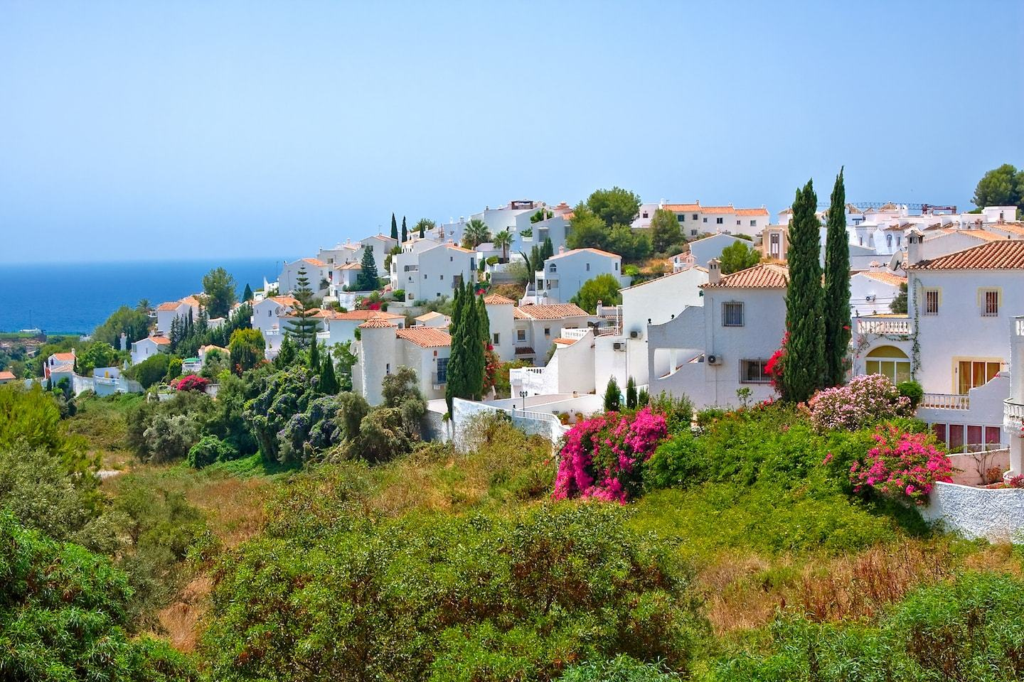 White houses sitting on green hills over ocean in Spain