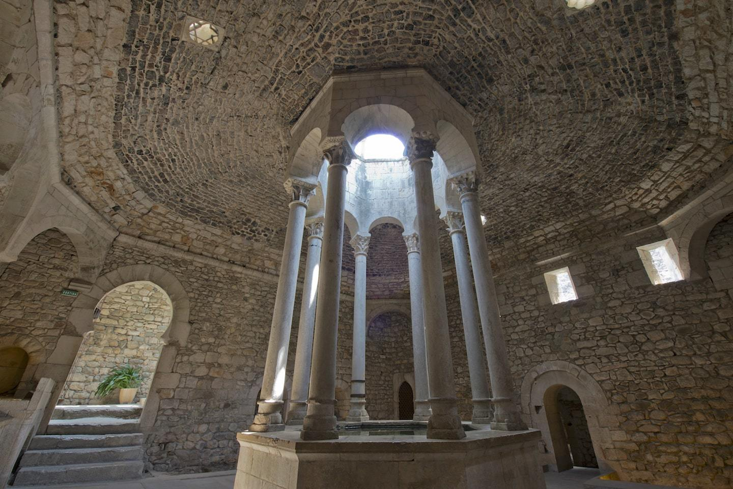 stone bath house with columns and light shining through