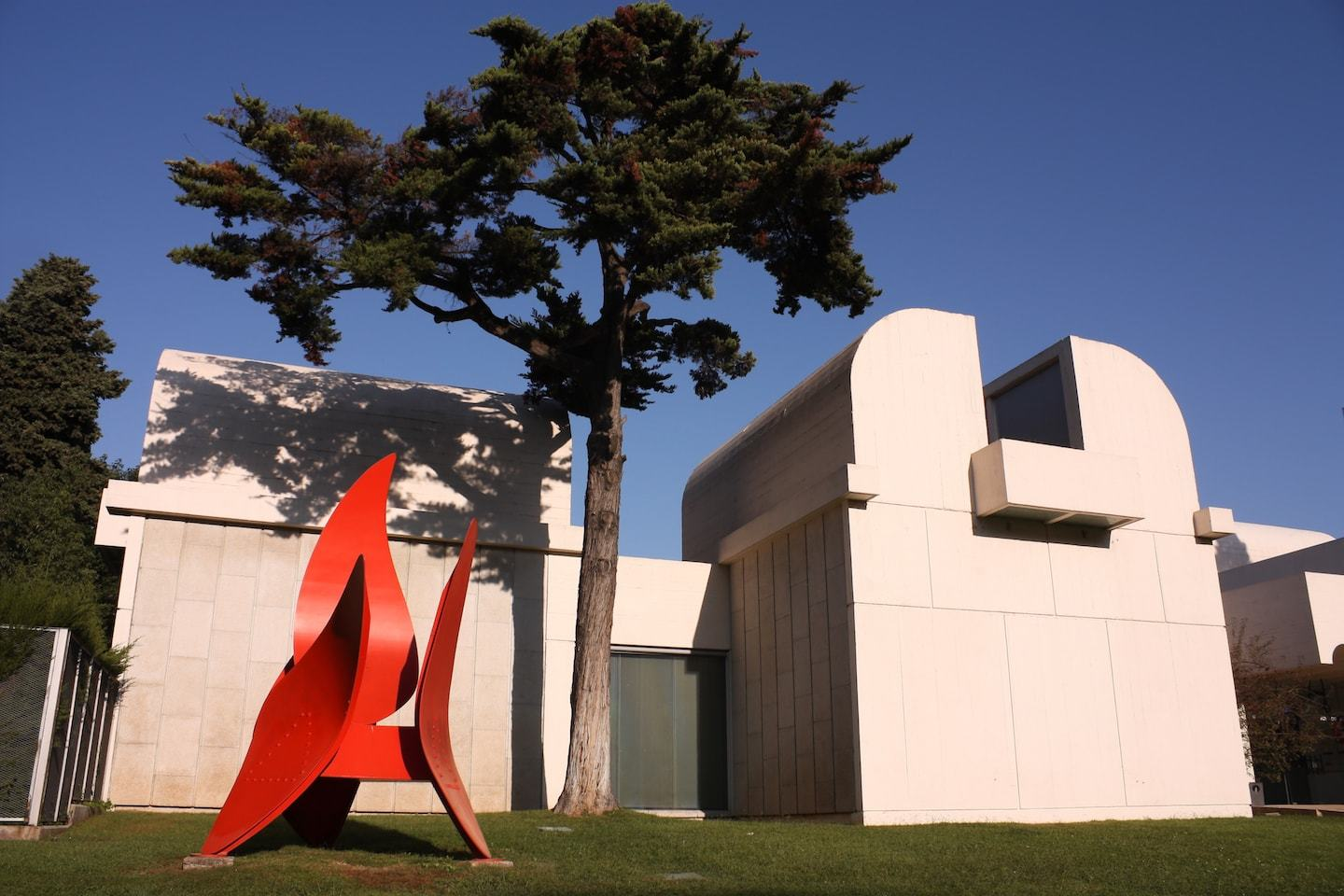 white barcelona museum with red sculpture outside