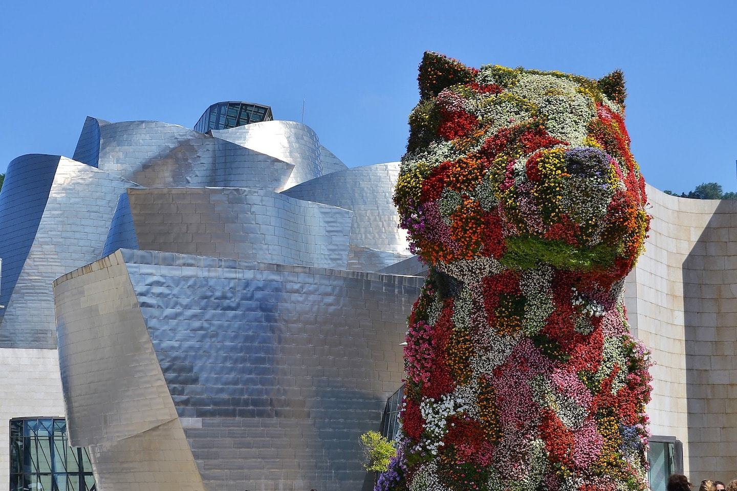 big sculpture of dog with flowers on it with modern metal building behind
