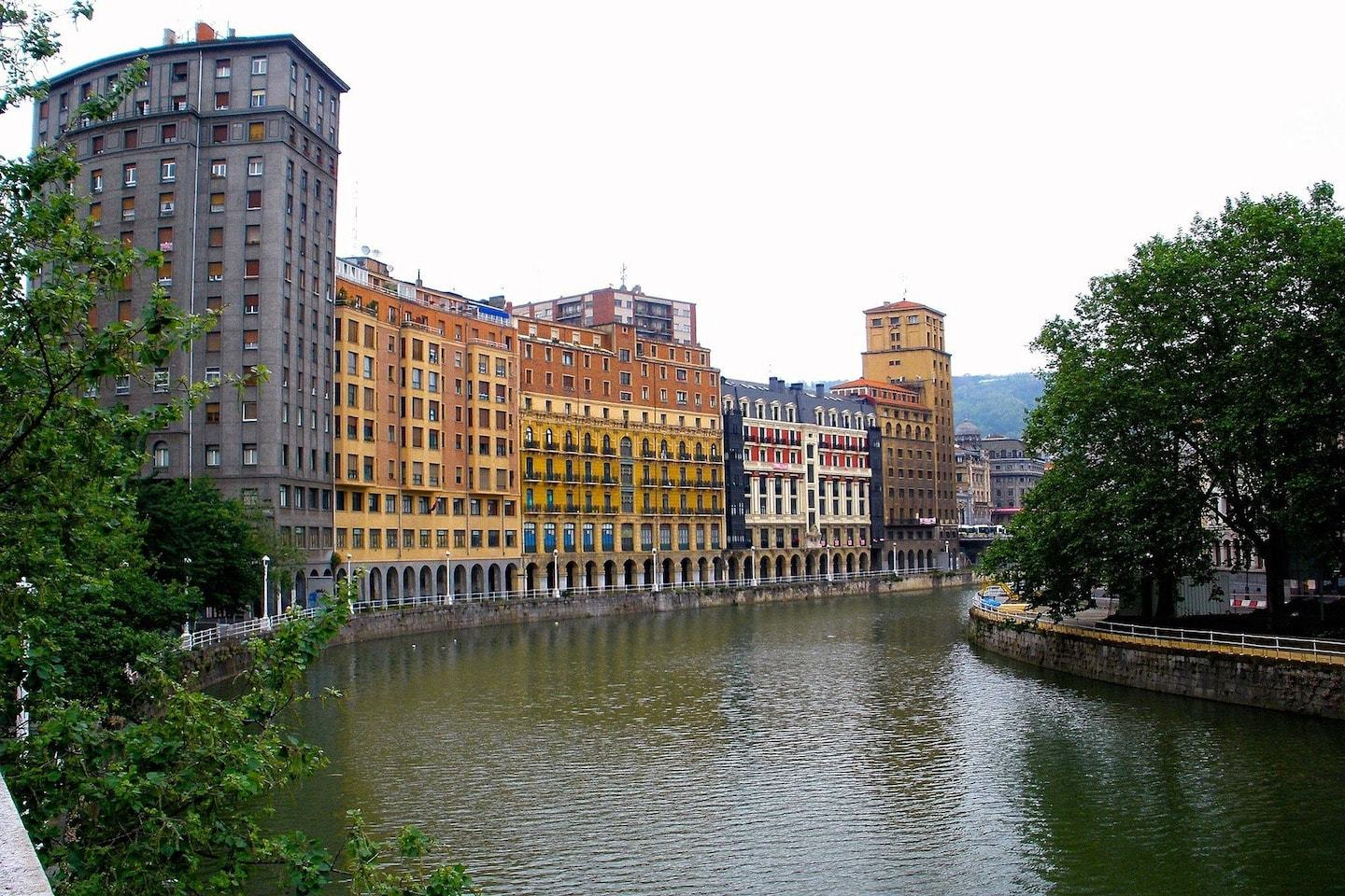 river with buildings on one side and trees on the other