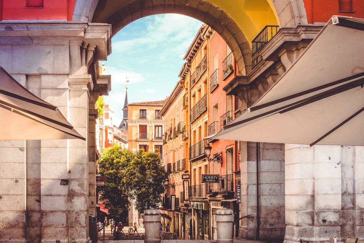 looking through arch at buildings with sun glow in madrid