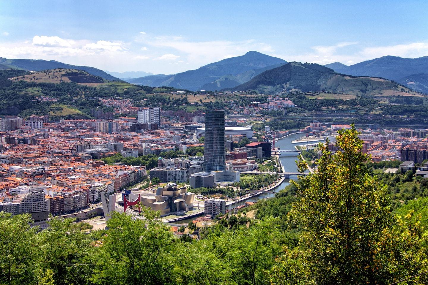 Aerial view of bilbao spain with buildings, trees and mountains