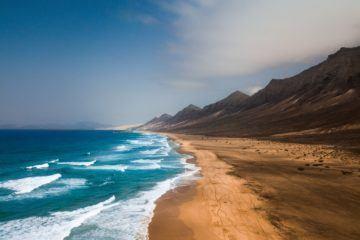 beach with rocky cliffs behind