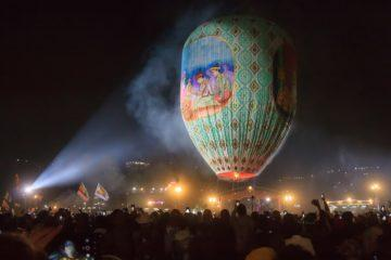 huge balloon floating in night sky with lights behind myanmar