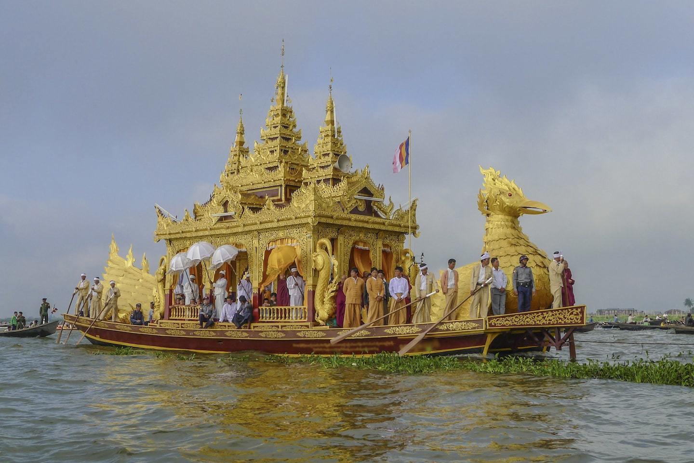golden boat rowing on lake myanmar