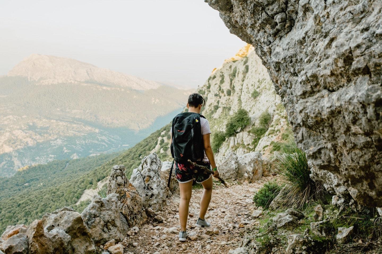 person trekking through rocky mountains in spain
