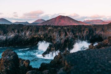cliffs with ocean crashing into it with red volcano in the background