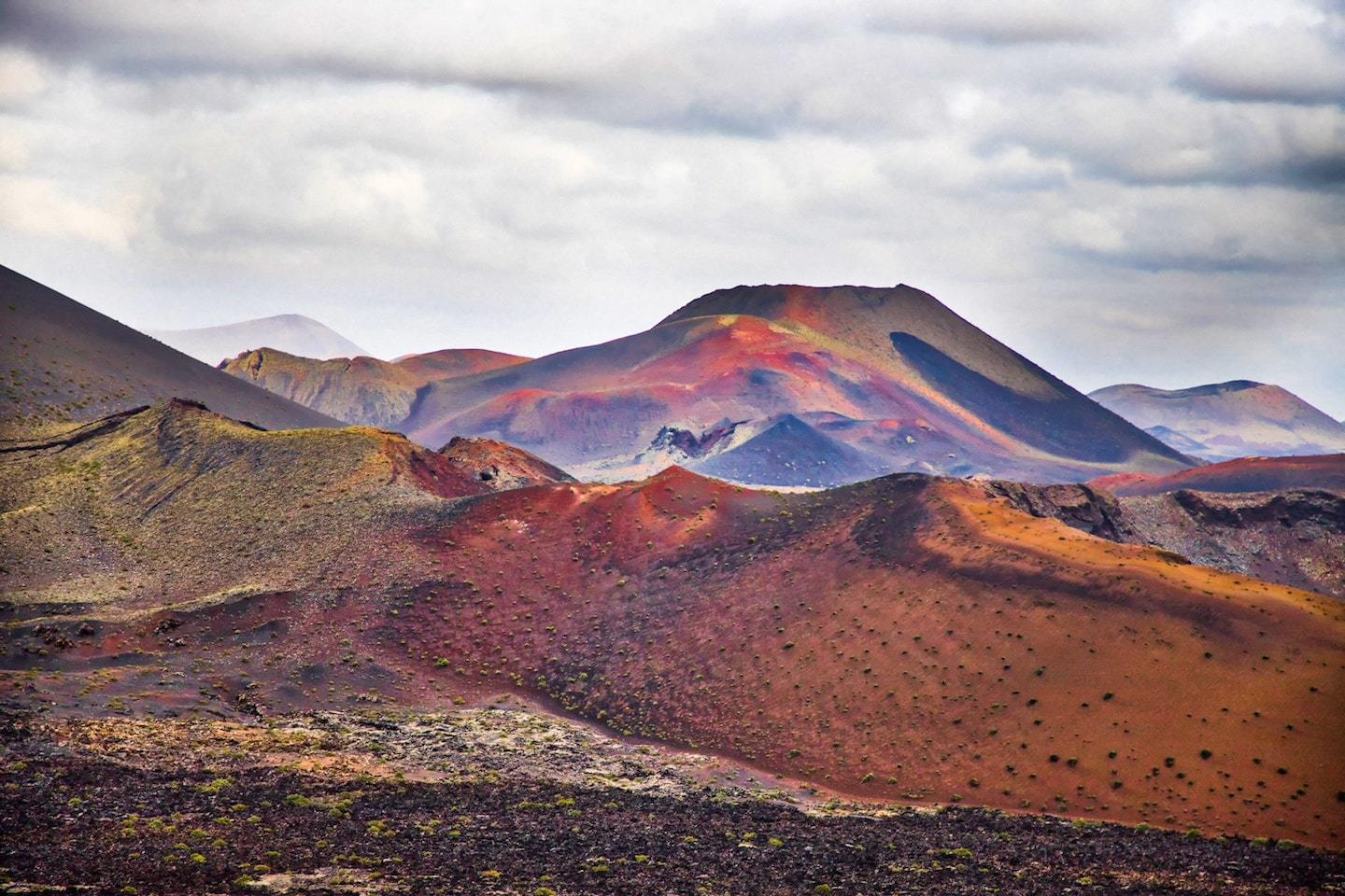 rainbow colored volcanic landscape with cloudy sky