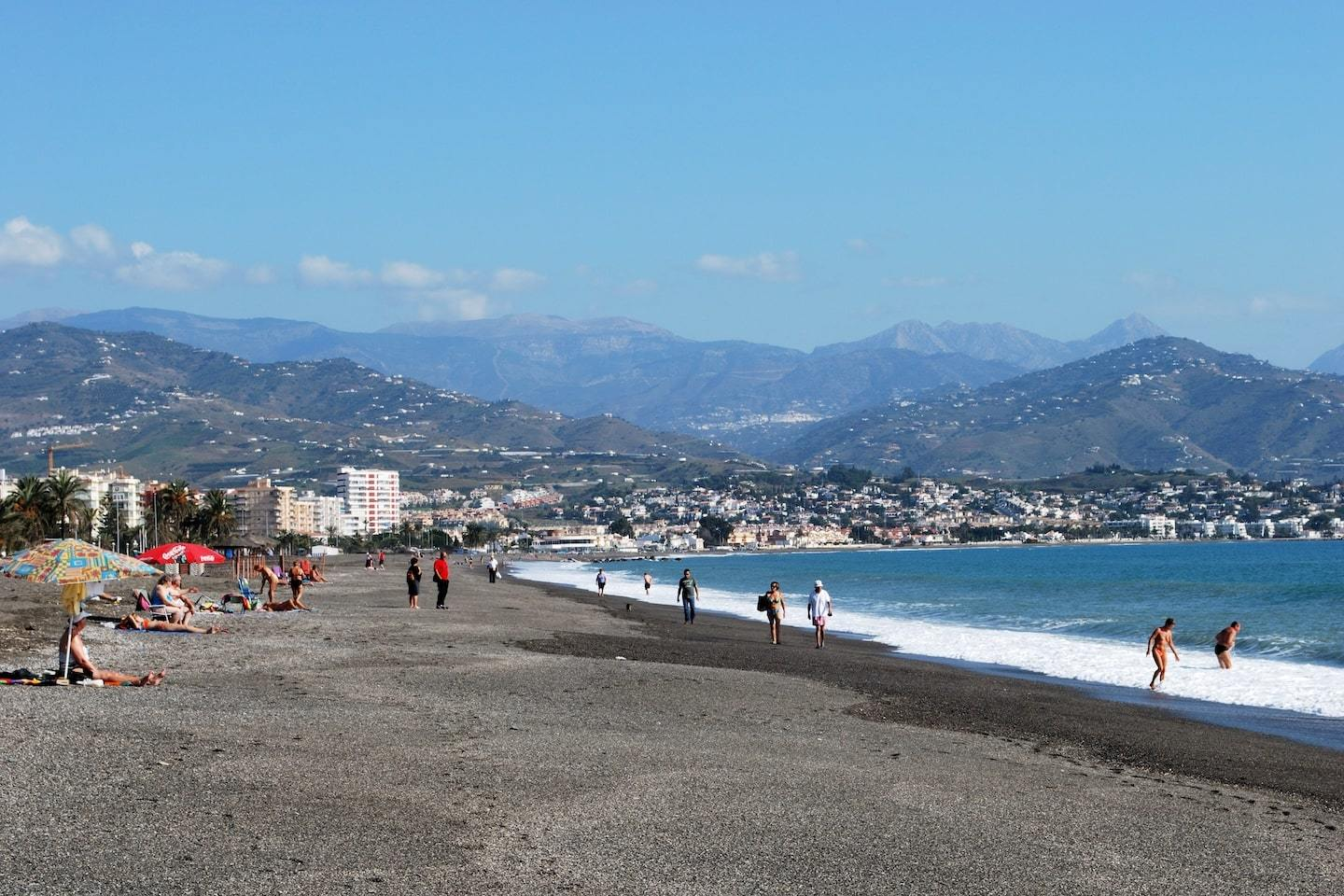 beach with dark sand and mountains behind