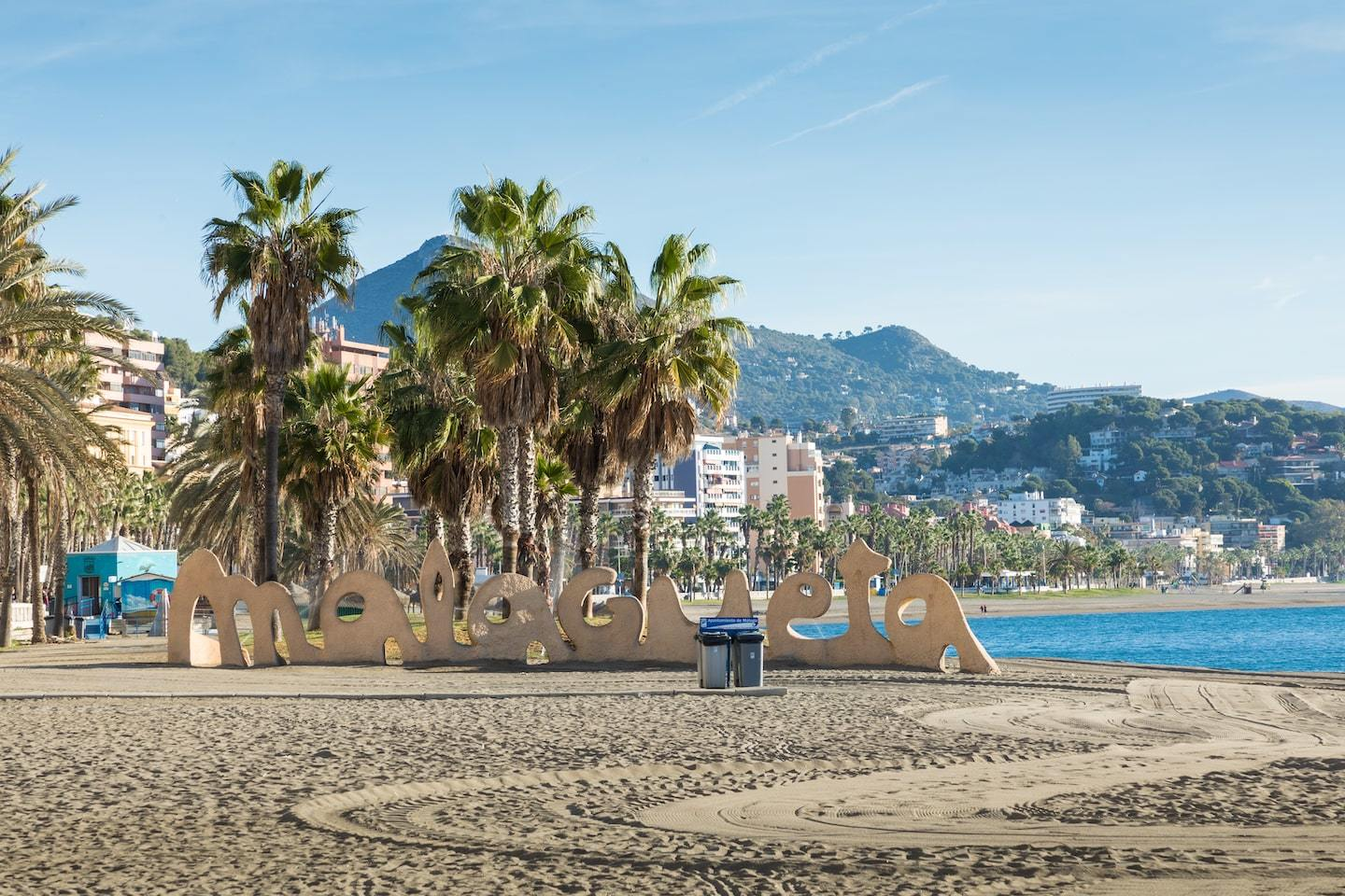 beach with large sign reading malagueta with palm trees and mountains behind