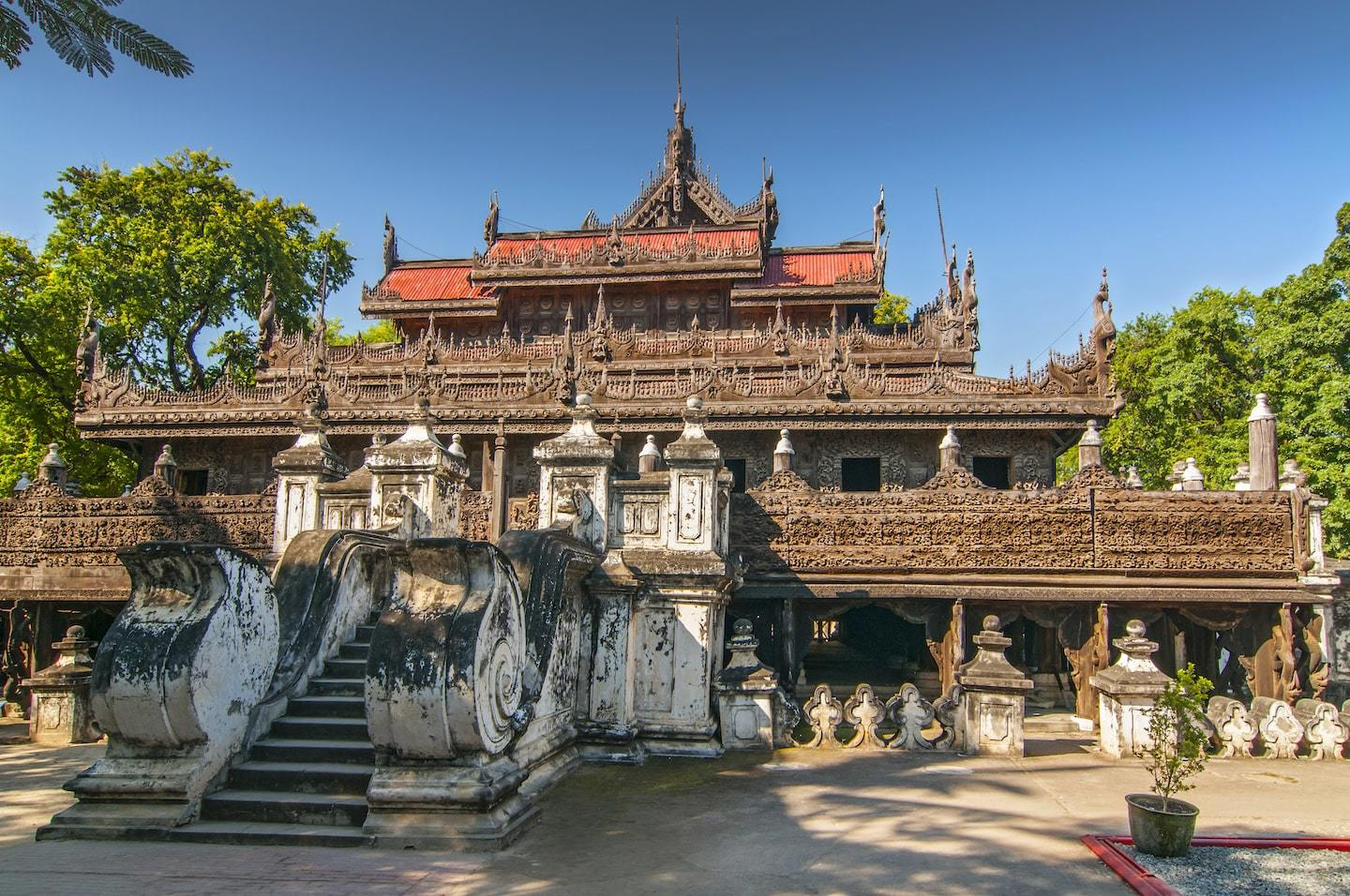 wooden monastery with statues in front and blue sky behind