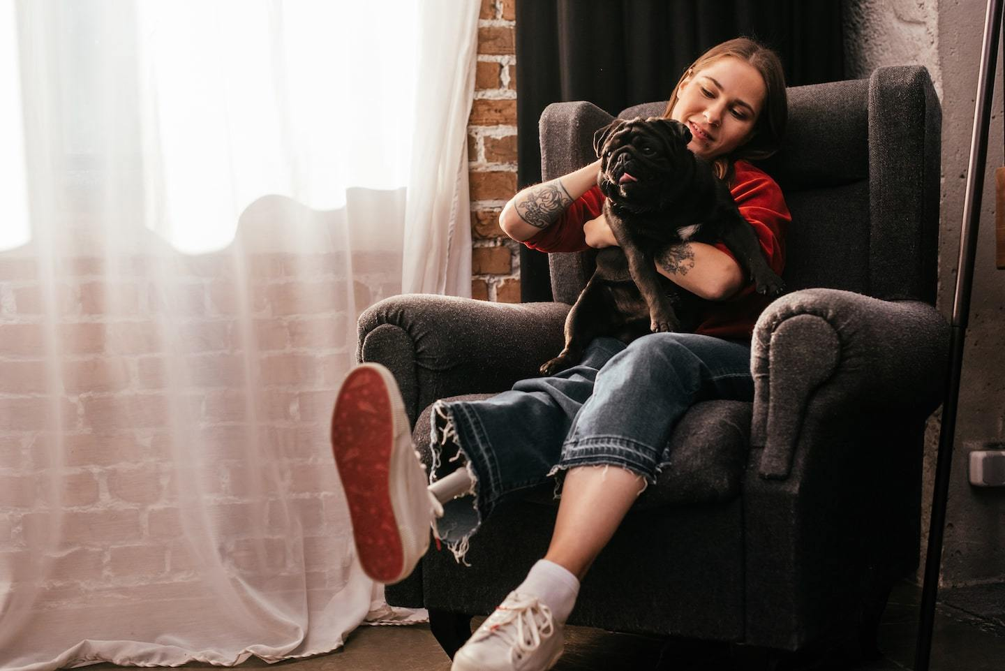 woman holding dog on her lap sitting in chair