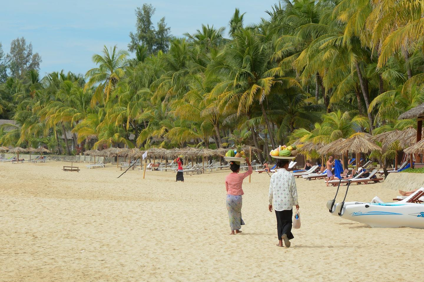 women walking with fruit baskets on their head along a beach with palm trees