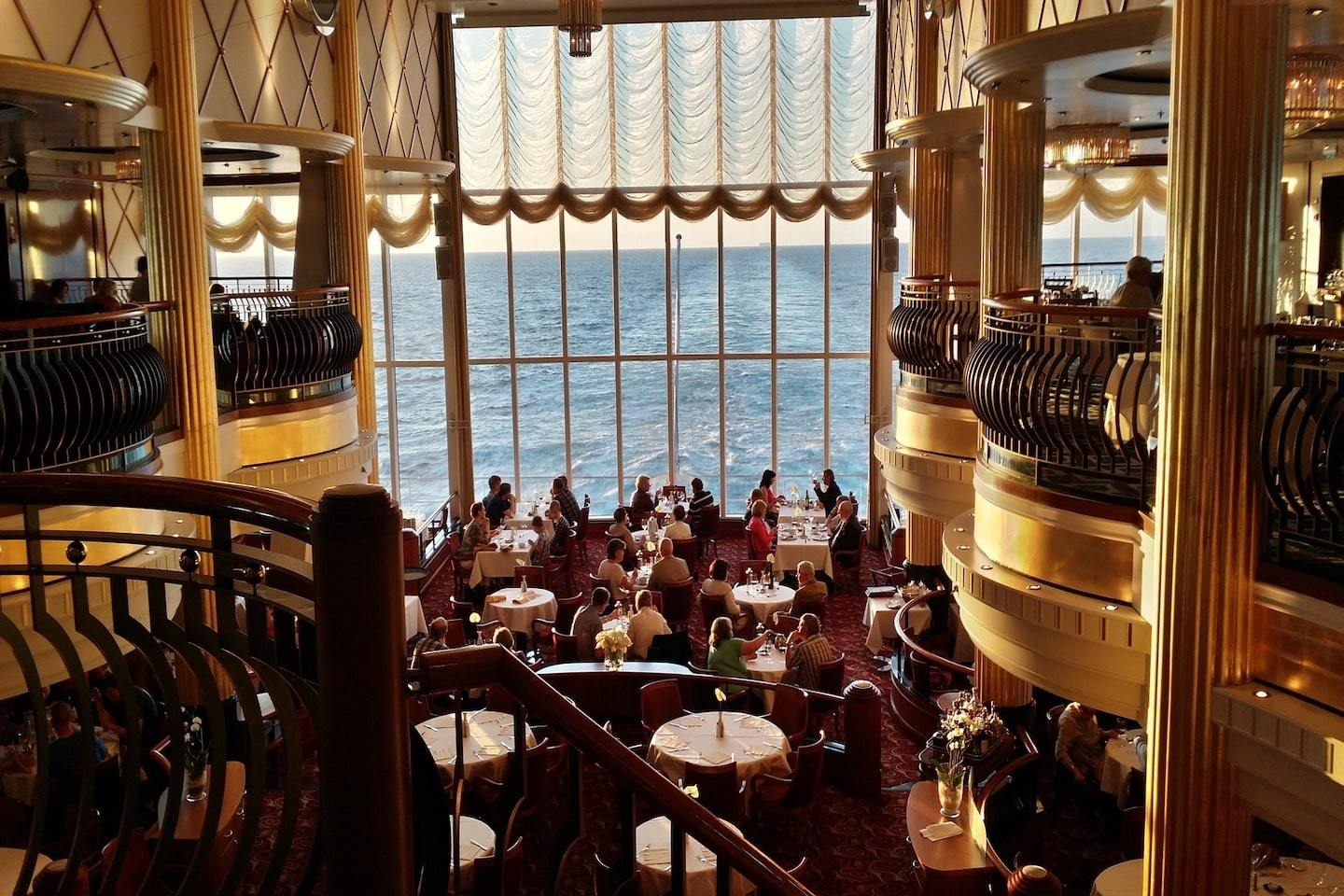 people dining at golden hour on a cruise ship with water outside of the window