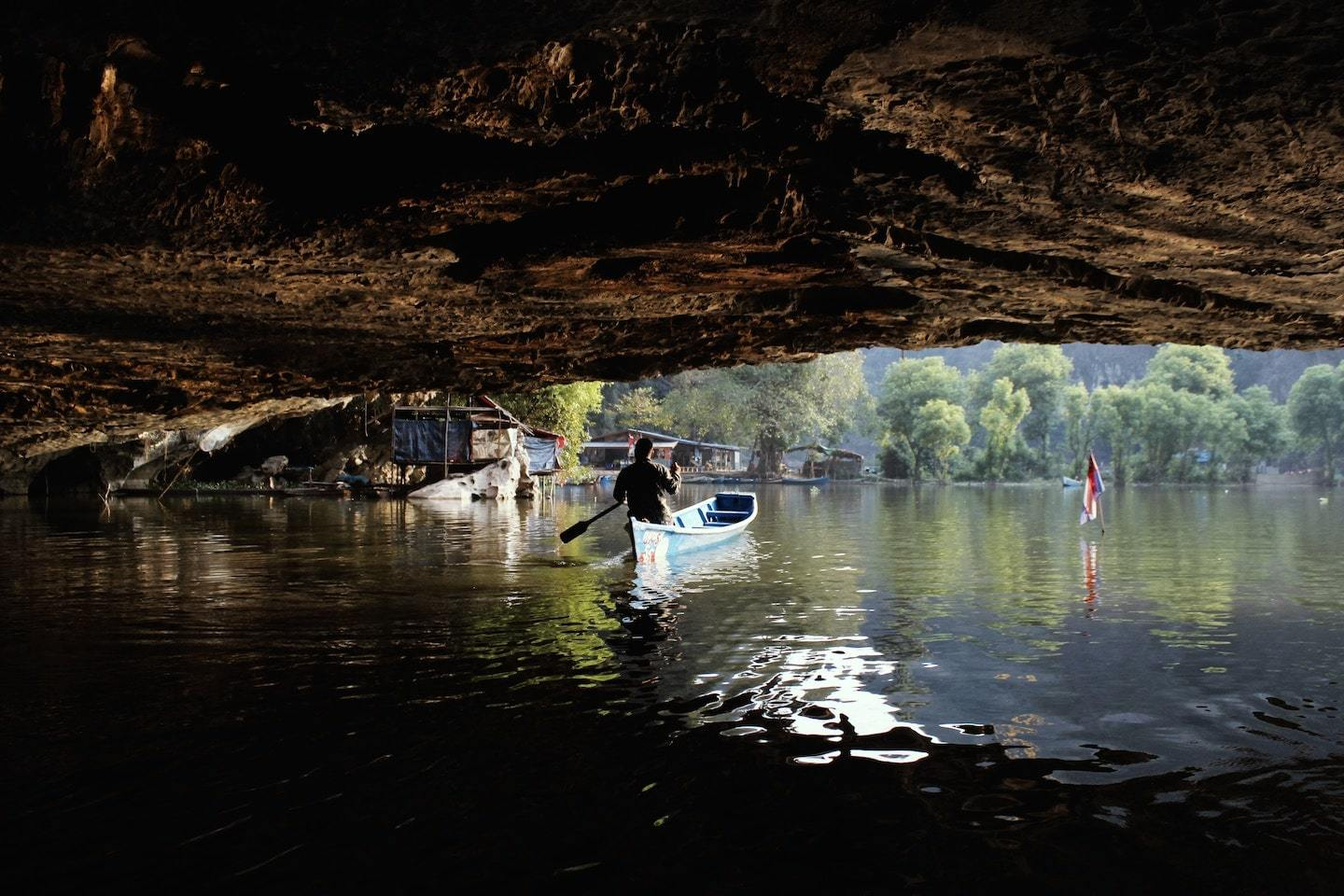 person rowing a boat through water in a cave