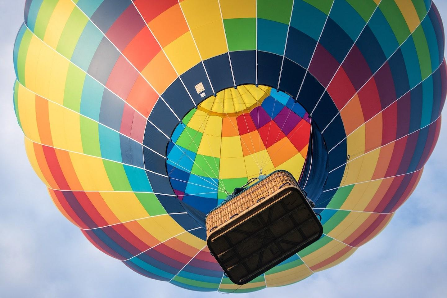view of rainbow hot air balloon in the sky from below