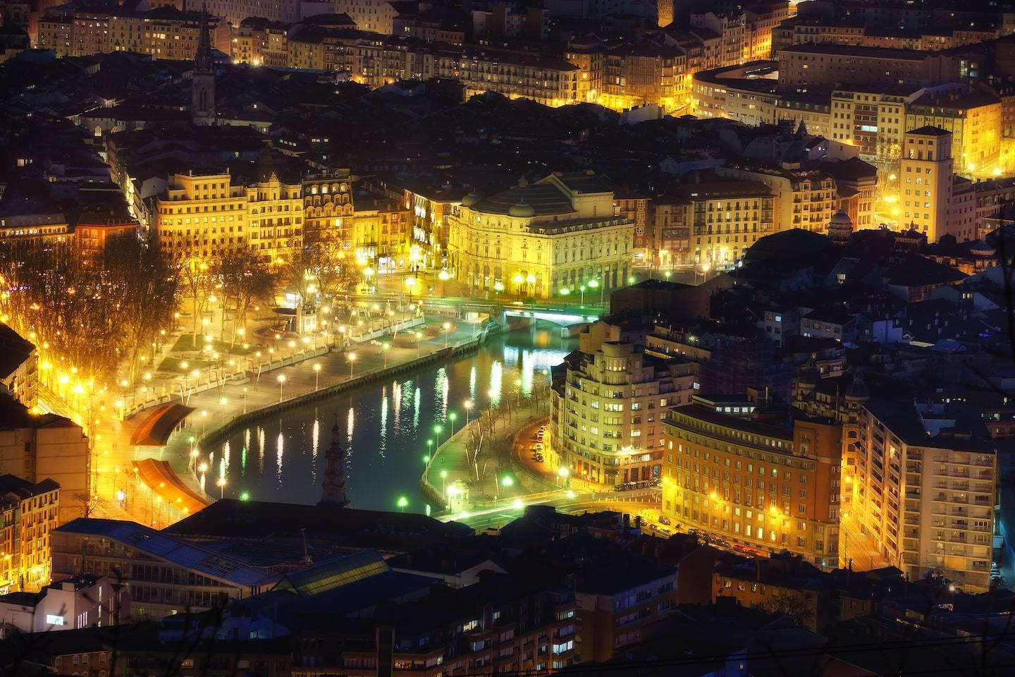 Aerial view of Bilbao at night with buildings lit up around the river