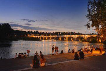 View of the Loire River in France at night with a bridge lit up.