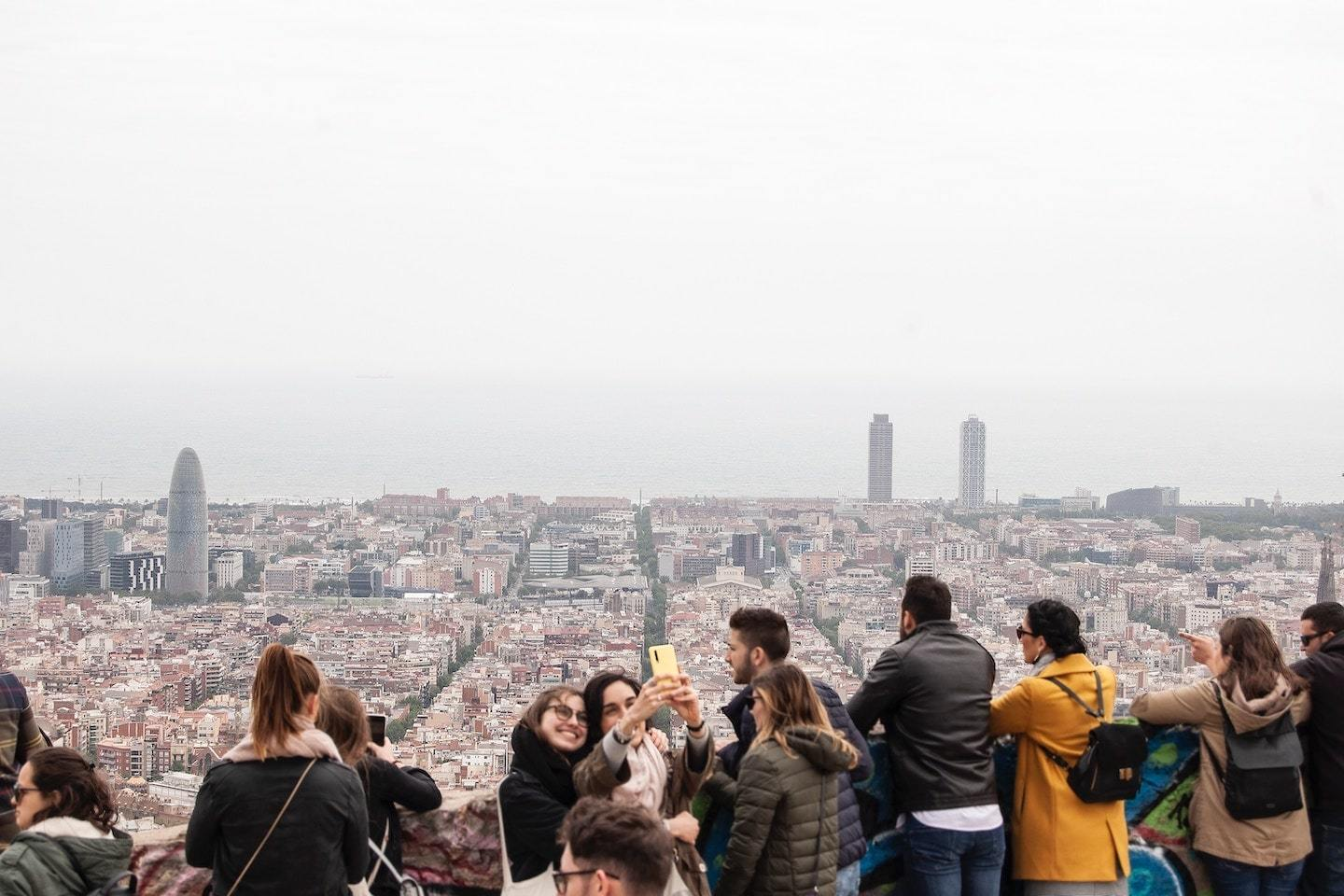 people taking selfies with Barcelona behind