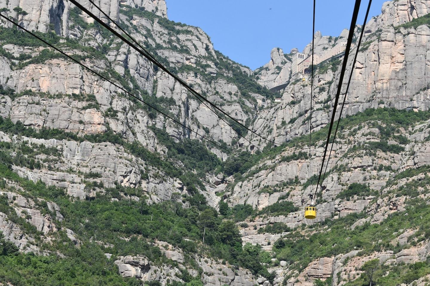 rocky green mountains with yellow cable car
